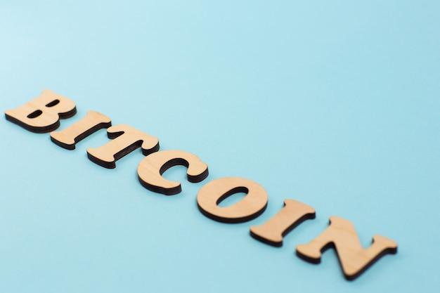 Bitcoin parola scritta sulla superficie blu con lettere in legno.