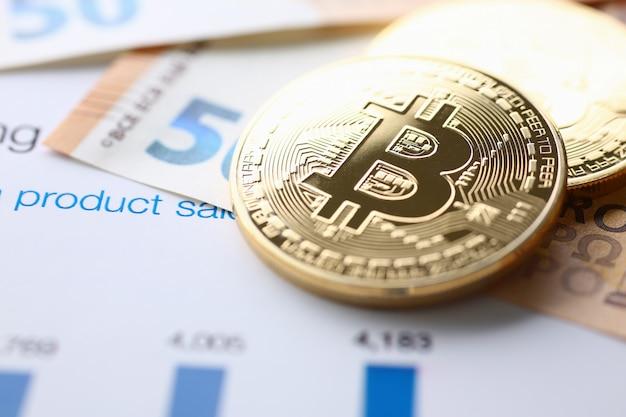Bitcoin e alcuni contanti che giacciono sui documenti