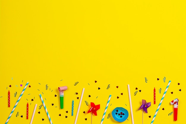 Decorazioni per feste di compleanno su sfondo giallo, vista dall'alto