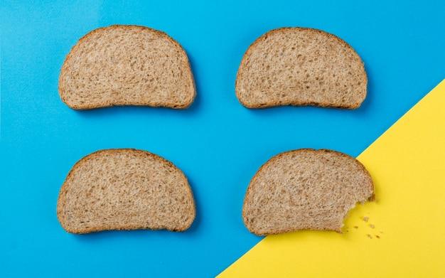 Pezzo di pane morso sul tavolo blu e giallo