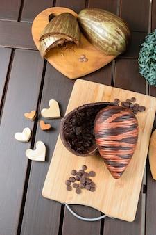 Uovo di pasqua di cioccolato amaro con croccante di mandorle, decorato con vernice commestibile, su una tavola di legno. circondato da callette di cioccolato, cuori di legno e uovo di cioccolato con ripieno di caramello.