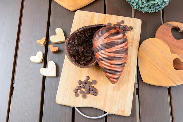 Uovo di pasqua di cioccolato amaro con croccante di mandorle, decorato con vernice commestibile, su una tavola di legno. circondato da callette di cioccolato e cuori di legno.