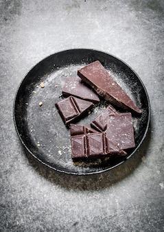 Cioccolato amaro nella vecchia padella. su sfondo di pietra. Foto Premium