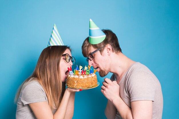 Bizzarro giovane coppia ragazza e ragazzo in cappelli di carta vogliono mordere un pezzo di torta di congratulazioni