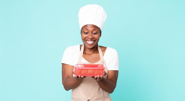 Donna chef adulta afroamericana nera con un tupperware