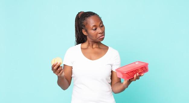 Donna adulta afroamericana nera che tiene un tupperware