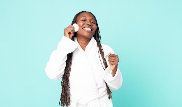 Donna adulta afroamericana nera che indossa accappatoio e tiene in mano un cotone per la pulizia del viso