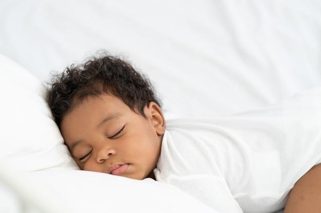 Bambino afroamericano nero che dorme su un materasso bianco.