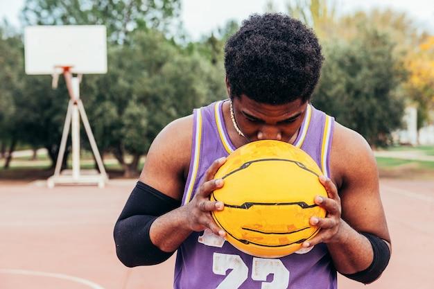 Ragazzo afroamericano nero che gioca pallacanestro su una corte. baciare una palla gialla. vestito con una camicia senza maniche viola