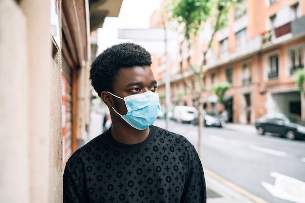 Ragazzo afroamericano nero che cammina per strada con una maschera blu che si protegge dalla pandemia di coronavirus covid-19