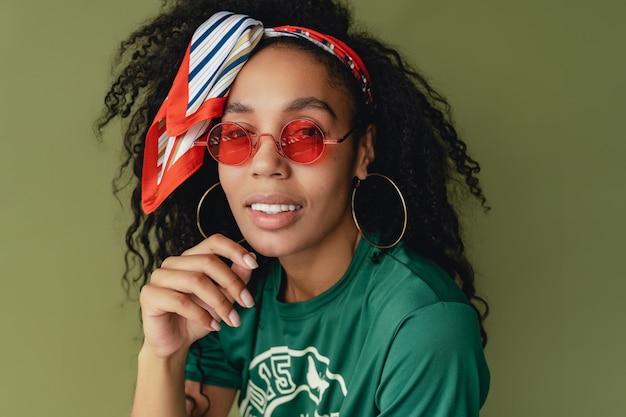 Donna afroamericana nera in t-shirt e pantaloncini alla moda hipster su verde