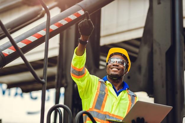 Lavoratore afroamericano nero come caposquadra del personale orgoglioso di sorridere felice che lavora il controllo del carico del carico nel magazzino logistico di spedizione con tuta di sicurezza.