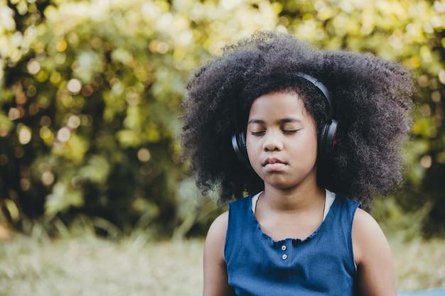 Bambine africane nere che usano le cuffie ascoltano musica con gli occhi chiusi, si concentrano e si concentrano al parco verde all'aperto