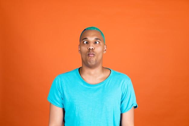L'uomo africano nero in casual sui capelli blu della parete arancione fa divertenti smorfie pazze pesce faccia divertendosi