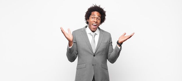 Uomo d'affari afro nero che si sente felice, eccitato, sorpreso o scioccato, sorridente e stupito da qualcosa di incredibile