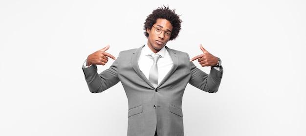 Uomo d'affari afro nero dall'aspetto orgoglioso, positivo e casual che punta al petto con entrambe le mani