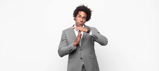 Uomo d'affari afro nero che sembra serio, severo, arrabbiato e dispiaciuto, facendo segno di time out