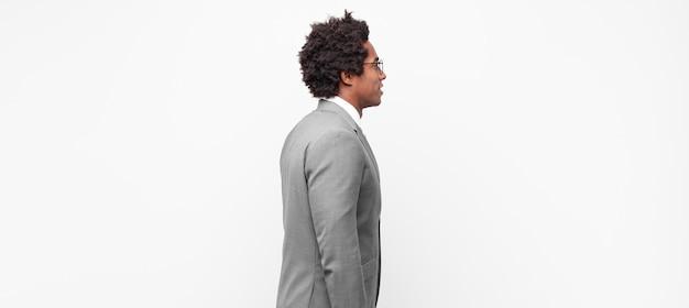 Black afro businessmanon vista di profilo cercando di copiare lo spazio avanti, pensando, immaginando o fantasticando