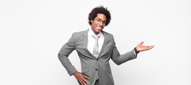 Uomo d'affari afro nero che sorride, si sente sicuro, di successo e felice, mostrando il concetto o l'idea sullo spazio della copia sul lato