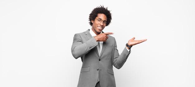 Uomo d'affari afro nero che sorride, si sente felice, spensierato e soddisfatto, indicando un concetto o un'idea sullo spazio della copia sul lato