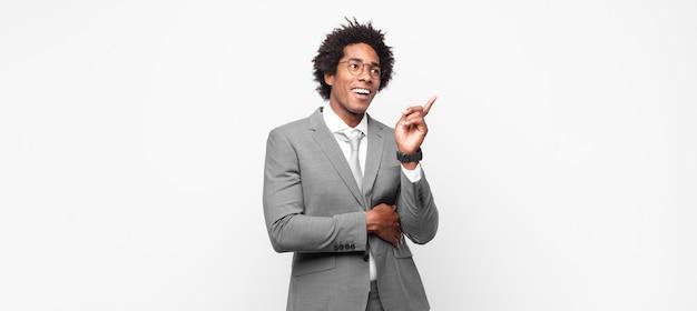 Uomo d'affari afro nero che sorride felice e guarda di traverso, chiedendosi, pensando o avendo un'idea