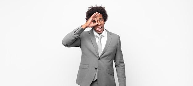 Uomo d'affari afro nero che sorride felicemente con una faccia buffa, scherza e guarda attraverso lo spioncino, spiando i segreti