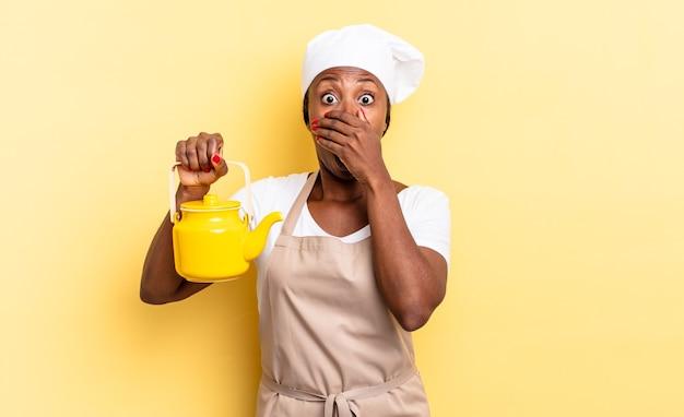 Donna chef afro nera che copre la bocca con le mani con un'espressione scioccata e sorpresa, mantenendo un segreto o dicendo oops. concetto di teiera