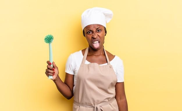 Donna chef afro nera che si sente disgustata e irritata, tira fuori la lingua, non ama qualcosa di brutto e schifoso. concetto di pulizia dei piatti