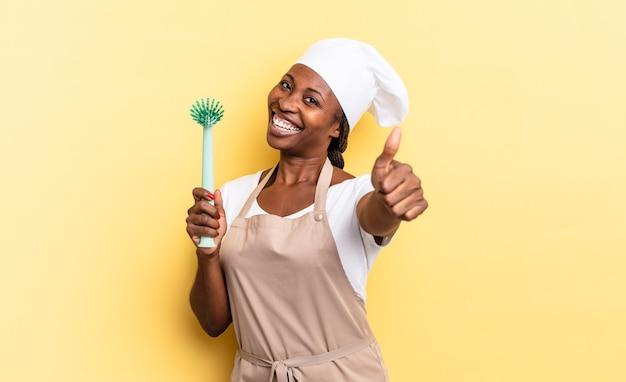 Donna chef afro nera che si sente orgogliosa, spensierata, sicura di sé e felice, sorridendo positivamente con i pollici in su. concetto di pulizia dei piatti