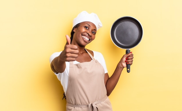 Donna chef afro nera che si sente orgogliosa, spensierata, sicura di sé e felice, sorridendo positivamente con il pollice in alto