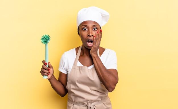Donna chef afro nera che si sente scioccata e spaventata, sembra terrorizzata con la bocca aperta e le mani sulle guance. concetto di pulizia dei piatti
