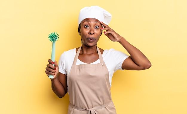 Donna chef afro nera che sembra felice, stupita e sorpresa, sorride e realizza buone notizie incredibili e incredibili. concetto di pulizia dei piatti
