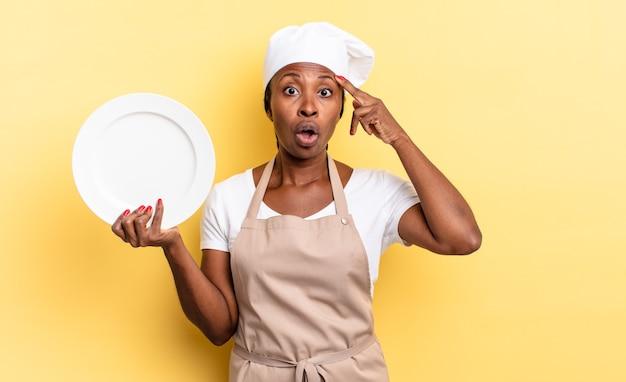 Donna chef afro nera che sembra sorpresa, a bocca aperta, scioccata, realizzando un nuovo pensiero, idea o concetto. concetto di piatto vuoto
