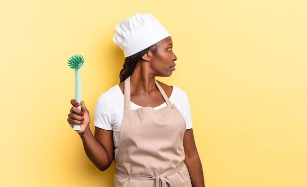 Donna chef afro nera sulla vista di profilo che cerca di copiare lo spazio avanti, pensando, immaginando o sognando ad occhi aperti. concetto di pulizia dei piatti