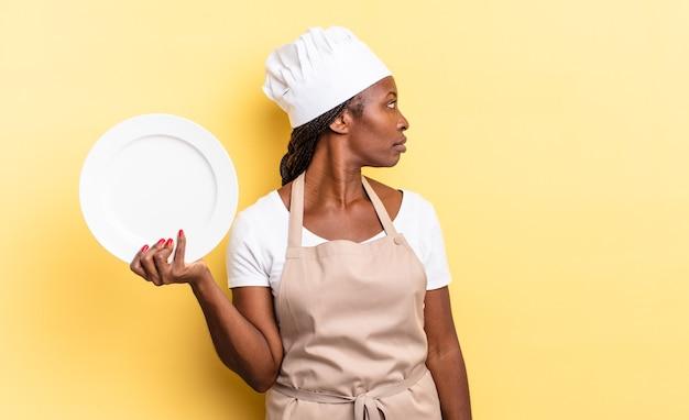 Donna chef afro nera sulla vista di profilo che cerca di copiare lo spazio avanti, pensando, immaginando o sognando ad occhi aperti. concetto di piatto vuoto