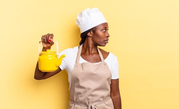 Donna chef afro nera sulla vista di profilo che cerca di copiare lo spazio avanti, pensando, immaginando o sognando ad occhi aperti. concetto di teiera