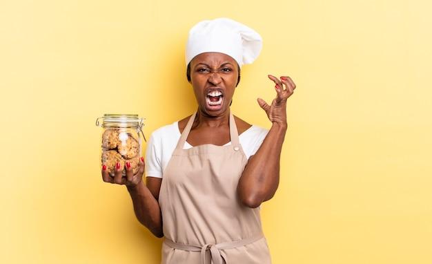 Donna chef afro nera che urla con le mani in alto, sentendosi furiosa, frustrata, stressata e turbata. concetto di biscotti