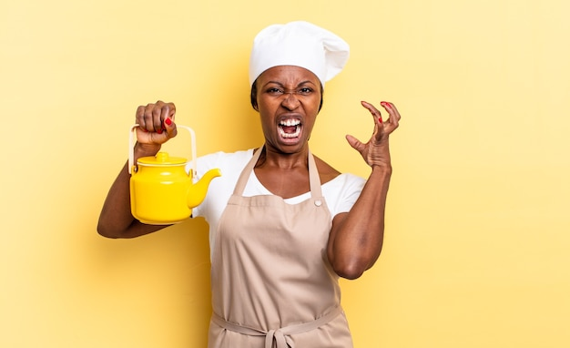 Donna chef afro nera che urla con le mani in alto, sentendosi furiosa, frustrata, stressata e turbata. concetto di teiera