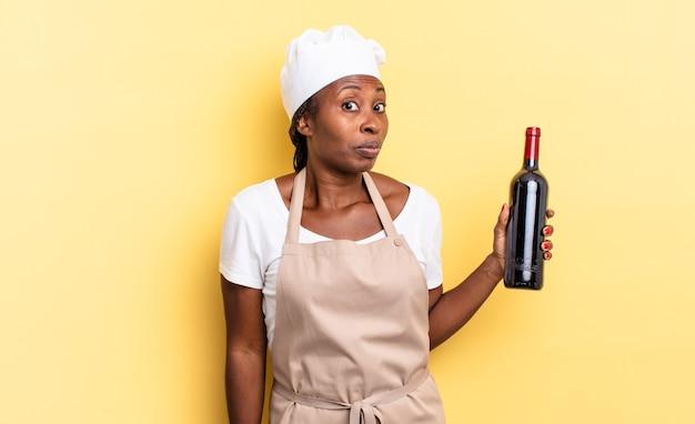 Donna chef afro nera che scrolla le spalle, si sente confusa e incerta, dubitando con le braccia incrociate e lo sguardo perplesso. concetto di bottiglia di vino