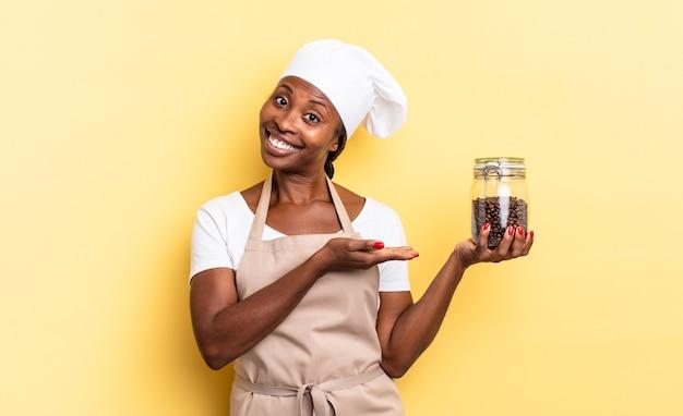 Donna chef afro nera che sorride allegramente, si sente felice e mostra un concetto nello spazio della copia con il palmo della mano. concetto di chicchi di caffè