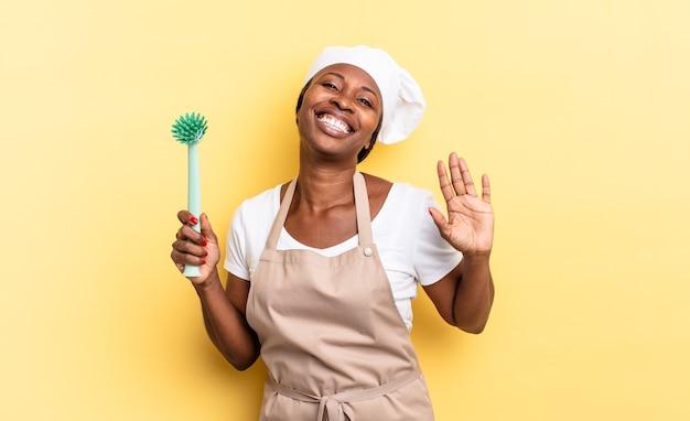 Donna chef afro nera che sorride allegramente e allegramente, agitando la mano, accogliendoti e salutandoti o salutandoti. concetto di pulizia dei piatti