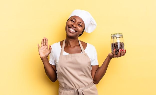 Donna chef afro nera che sorride allegramente e allegramente, agitando la mano, accogliendoti e salutandoti o salutandoti. concetto di chicchi di caffè