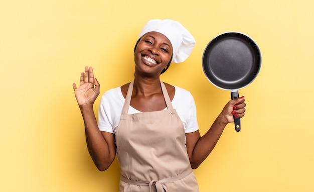 Donna chef afro nera che sorride allegramente e allegramente, agitando la mano, accogliendoti e salutandoti, o salutandoti
