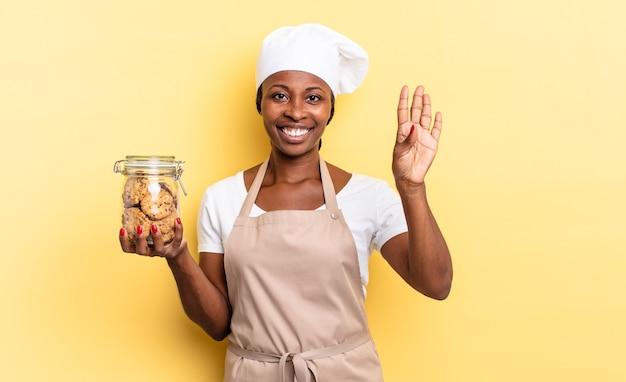 Nero chef afro donna sorridente e dall'aspetto amichevole, mostrando il numero quattro o il quarto con la mano in avanti, conto alla rovescia. concetto di biscotti