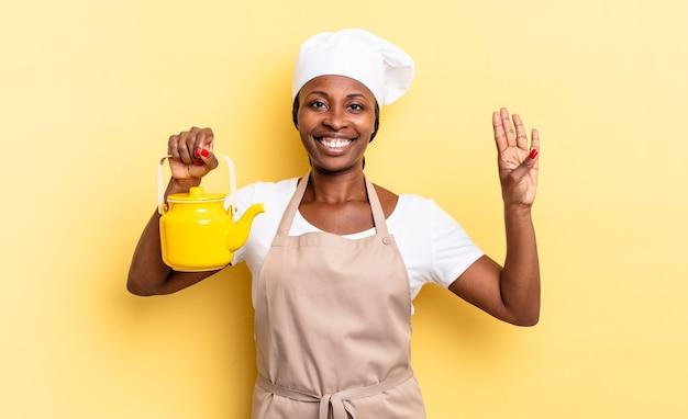 Nero chef afro donna sorridente e dall'aspetto amichevole, mostrando il numero quattro o il quarto con la mano in avanti, conto alla rovescia. concetto di teiera
