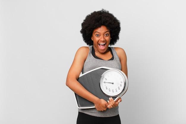 Donna fitness afro nera con un equilibrio o una bilancia