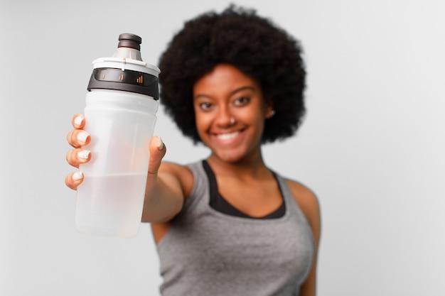 Donna fitness afro nera con asciugamano e tanica d'acqua