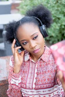 Ragazza afro nera in abito etnico con le cuffie seduto in un caffè all'aperto, ascoltando musica e facendo selfie su smartphone