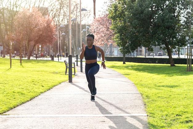 Ragazza afro nera che corre in un parco pubblico al tramonto