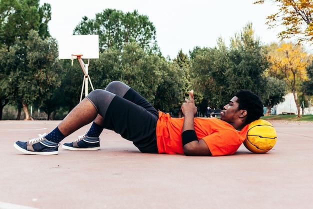 Ragazzo afro nero sdraiato sulla sua palla sul campo da basket mentre usa il suo telefono cellulare. concetto di tecnologia e sport.